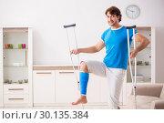 Купить «Leg injured young man with crutches at home», фото № 30135384, снято 19 сентября 2018 г. (c) Elnur / Фотобанк Лори