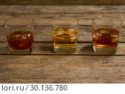 Купить «Three glasses of whiskey with ice cube», фото № 30136780, снято 11 января 2017 г. (c) Wavebreak Media / Фотобанк Лори