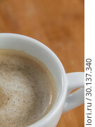 Close-up of white coffee cup with creamy froth. Стоковое фото, агентство Wavebreak Media / Фотобанк Лори