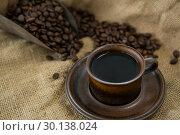 Купить «Black coffee, roasted beans and scoop on sack», фото № 30138024, снято 6 октября 2016 г. (c) Wavebreak Media / Фотобанк Лори