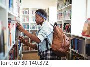 Купить «Schoolgirl selecting book from book shelf in library», фото № 30140372, снято 19 ноября 2016 г. (c) Wavebreak Media / Фотобанк Лори