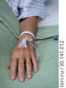 Senior patient hand with saline on bed in hospital. Стоковое фото, агентство Wavebreak Media / Фотобанк Лори