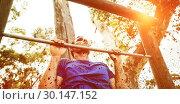 Купить «Fit man doing pull ups on bar during obstacle course», фото № 30147152, снято 24 ноября 2016 г. (c) Wavebreak Media / Фотобанк Лори