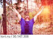 Купить «Happy man raising his hands during obstacle course», фото № 30147308, снято 24 ноября 2016 г. (c) Wavebreak Media / Фотобанк Лори