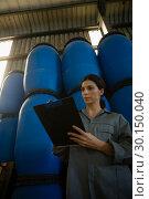 Купить «Female worker writing on clipboard in olive factory», фото № 30150040, снято 22 марта 2017 г. (c) Wavebreak Media / Фотобанк Лори