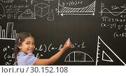 Girl writing with chalk on blackboard with math equations. Стоковое фото, агентство Wavebreak Media / Фотобанк Лори