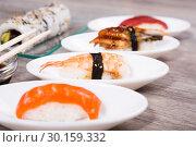 Купить «four kinds Nigirisushi on oval saucers and Uramaki», фото № 30159332, снято 25 октября 2016 г. (c) Татьяна Яцевич / Фотобанк Лори