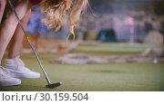 Купить «A young woman playing mini golf indoors. Legs in the frame», видеоролик № 30159504, снято 25 марта 2019 г. (c) Константин Шишкин / Фотобанк Лори