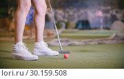 Купить «A young woman playing mini golf. Legs in the frame», видеоролик № 30159508, снято 25 марта 2019 г. (c) Константин Шишкин / Фотобанк Лори
