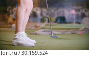 Купить «A young woman playing mini golf indoors. Feet in white sneakers», видеоролик № 30159524, снято 29 мая 2020 г. (c) Константин Шишкин / Фотобанк Лори