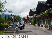 Купить «Garmisch-Partenkirchen, Germany, Traditional residential buildings along the Fruehlingstrasse», фото № 30159928, снято 31 мая 2016 г. (c) Caro Photoagency / Фотобанк Лори