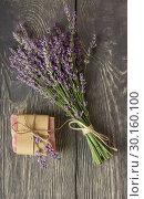 Купить «Fresh fragrant bundle of lavender and handmade soaps against dark boards», фото № 30160100, снято 20 июня 2018 г. (c) Сергей Молодиков / Фотобанк Лори