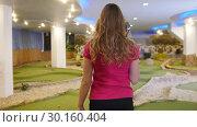 Купить «Playing mini golf. A young blonde woman takes a golf stick from the bag and goes away», видеоролик № 30160404, снято 25 марта 2019 г. (c) Константин Шишкин / Фотобанк Лори