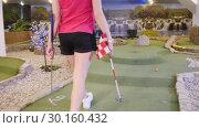 Купить «A young woman playing mini golf. Taking a finish flag and swaps the finish hole», видеоролик № 30160432, снято 25 марта 2019 г. (c) Константин Шишкин / Фотобанк Лори