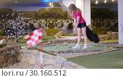 Купить «A young woman playing mini golf. A woman hitting several golf balls in a row», видеоролик № 30160512, снято 25 марта 2019 г. (c) Константин Шишкин / Фотобанк Лори
