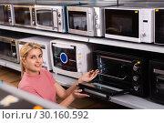 Купить «Positive female looking new microwave for kitchen in furniture store», фото № 30160592, снято 1 марта 2018 г. (c) Яков Филимонов / Фотобанк Лори