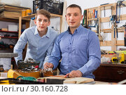 Купить «Portrait of woodworker and pupil cutting wooden plank with fret saw», фото № 30160728, снято 17 мая 2017 г. (c) Яков Филимонов / Фотобанк Лори