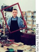 Купить «portrait of man in uniform choosing tight wooden bar in picture framing atelier», фото № 30160744, снято 17 мая 2017 г. (c) Яков Филимонов / Фотобанк Лори