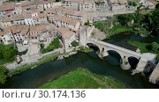 Купить «Aerial view of historic centre of Besalu with Romanesque bridge over Fluvia river, Catalonia, Spain», видеоролик № 30174136, снято 11 июня 2018 г. (c) Яков Филимонов / Фотобанк Лори