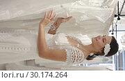 Сheerful young woman dressed in luxury white gown standing in wedding shop. Стоковое видео, видеограф Яков Филимонов / Фотобанк Лори