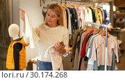 Купить «Young blonde woman choosing baby clothes small size in shop», видеоролик № 30174268, снято 13 ноября 2018 г. (c) Яков Филимонов / Фотобанк Лори