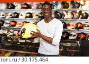 Купить «Portrait of young Afro man satisfied with new riding gear at motorcycle shop», фото № 30175464, снято 16 января 2019 г. (c) Яков Филимонов / Фотобанк Лори