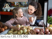 portret of young woman with beautiful blonde daughter choosing onions at store. Стоковое фото, фотограф Татьяна Яцевич / Фотобанк Лори