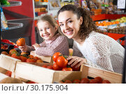 portret of young woman with beautiful daughter choosing tomatoes at store. Стоковое фото, фотограф Татьяна Яцевич / Фотобанк Лори
