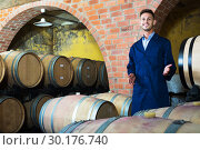 portrait of young male wine maker in coat working in winery cellaryoung wine maker in cellarman, male, young, working, winery, wine, cellar, wood, aging, standing, looking, expert, manufactory, uniform, bottler, equipment, section, alcohol, beverage, winemaking, professional, occupation, small, tank, processing, barrel, compartment, container, positive, european, caucasian, 20s, 30-35, portrait, examining, cheerful, glad, production, taste, factory, employed, showing, visiting, coveralls, unit, one, promoting, checking, coat, quality, control, craft, man, male, young,working, winery, wine, standing, cellar, wood, aging, looking, expert, manufactory, uniform, bottler, equipment, section, alcohol, bottle, beverage, winemaking, professional, occupation, processing, barrel, compartment, container, positive, caucasian, american, 30s, 25-29, expertise, smiling, producer, one, segment, label, selective, check-up, attentive, leaning, Стоковое фото, фотограф Яков Филимонов / Фотобанк Лори