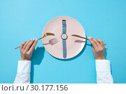 Купить «Wristwatch with six o'clock and woman's hand with fork and knite on a blue background. Time to lose weight, eating control or diet concept. Flat lay.», фото № 30177156, снято 5 февраля 2019 г. (c) Ярослав Данильченко / Фотобанк Лори