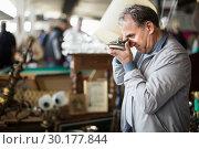 Купить «Senior man choosing vintage goods at flea market», фото № 30177844, снято 23 октября 2017 г. (c) Яков Филимонов / Фотобанк Лори