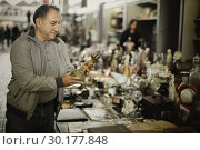 Купить «Senior man is looking ancient lamp at the fleamarket», фото № 30177848, снято 23 октября 2017 г. (c) Яков Филимонов / Фотобанк Лори