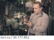 Купить «Adult male is choosing lamp at the market of old things.», фото № 30177852, снято 23 октября 2017 г. (c) Яков Филимонов / Фотобанк Лори