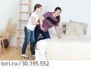 Девочка помогает своей беременной матери лечь на кровать при внезапных болях в животе. Стоковое фото, фотограф Кекяляйнен Андрей / Фотобанк Лори