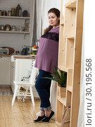 Pregnant European woman standing in kitchen, looking at camera, full length portrait. Стоковое фото, фотограф Кекяляйнен Андрей / Фотобанк Лори