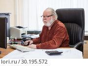 Купить «Пожилой мужчина в очках работает за компьютером в офисе», фото № 30195572, снято 22 февраля 2019 г. (c) Кекяляйнен Андрей / Фотобанк Лори