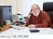 Мужчина пенсионного возраста разговаривает по телефону на работе. Стоковое фото, фотограф Кекяляйнен Андрей / Фотобанк Лори