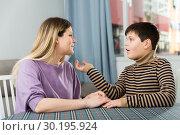 Купить «Portrait of young woman and son chatting at table», фото № 30195924, снято 9 февраля 2019 г. (c) Яков Филимонов / Фотобанк Лори