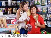 Купить «boy with mother choosing dog treats for their puppy», фото № 30195980, снято 22 августа 2018 г. (c) Яков Филимонов / Фотобанк Лори