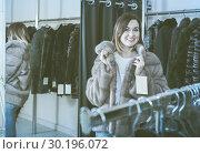 Купить «woman trying on fur coat in women's cloths store», фото № 30196072, снято 21 марта 2019 г. (c) Яков Филимонов / Фотобанк Лори