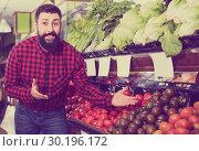 Купить «Male seller standing near the shelves with tomatoes», фото № 30196172, снято 15 ноября 2016 г. (c) Яков Филимонов / Фотобанк Лори
