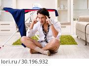 Купить «Young man ironing in the bedroom», фото № 30196932, снято 29 ноября 2018 г. (c) Elnur / Фотобанк Лори