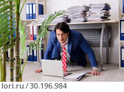 Купить «Young businessman employee unhappy with excessive work», фото № 30196984, снято 27 декабря 2018 г. (c) Elnur / Фотобанк Лори