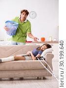 Купить «Husband helping leg injured wife in housework», фото № 30199640, снято 4 октября 2018 г. (c) Elnur / Фотобанк Лори
