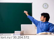 Young male teacher in front of chalkboard. Стоковое фото, фотограф Elnur / Фотобанк Лори