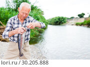 Купить «Adult fisherman removing catch from hook», фото № 30205888, снято 10 июня 2018 г. (c) Яков Филимонов / Фотобанк Лори