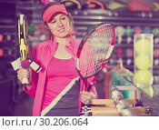 Купить «smiling sporty woman in uniform is holding new racket for padel and tennis in the store», фото № 30206064, снято 7 февраля 2018 г. (c) Яков Филимонов / Фотобанк Лори
