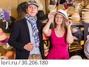 Купить «Woman and man trying on fashion hats», фото № 30206180, снято 2 мая 2017 г. (c) Яков Филимонов / Фотобанк Лори