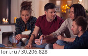 Купить «friends playing cards game at home in evening», видеоролик № 30206828, снято 12 января 2019 г. (c) Syda Productions / Фотобанк Лори
