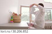 Купить «happy pregnant woman setting baby clothes at home», видеоролик № 30206852, снято 19 февраля 2019 г. (c) Syda Productions / Фотобанк Лори